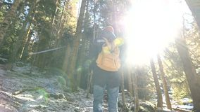 Tracking camera Low wide angle rear view of a male traveler with a backpack walking along a path in a coniferous forest. In winter. The concept of finding your stock video
