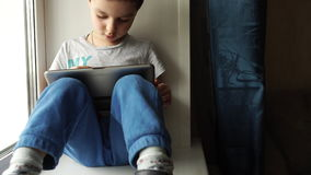 TRACKING: Child sits on a windowsill and uses a digital tablet pc. TRACKING: Child sits on windowsill and uses a digital tablet pc stock video footage