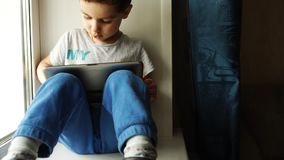 TRACKING: Cute Boy Playing The Tablet PC And Sitting On A Windowsill In The Room stock video footage