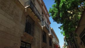Looking Up at Balconies in Havana Cuba Narrow Streets. 8879 A tracking dolly shot looking up at the balconies on buildings on a typical narrow street in Havana`s stock footage