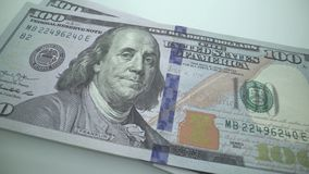 Tracking macro of Benjamine Franklin`s face on the US one hundreed dollar bill. US dollars background stock footage