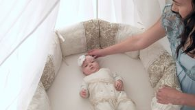 Tracking mother putting baby to sleep while walking . Attractive woman holding baby in hands and walk across living room. Tracking mother putting baby to sleep Royalty Free Stock Photos