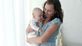 Tracking mother putting baby to sleep while walking . Attractive woman holding baby in hands and walk across living room. Tracking mother putting baby to sleep Royalty Free Stock Photography