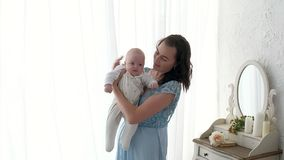 Tracking mother putting baby to sleep while walking . Attractive woman holding baby in hands and walk across living room. Tracking mother putting baby to sleep Royalty Free Stock Photo