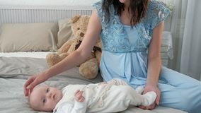 Tracking mother putting baby to sleep while walking . Attractive woman holding baby in hands and walk across living room. Tracking mother putting baby to sleep Stock Photography
