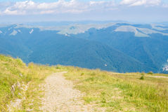 A tracking path over the mountain at Carpatians and beautiful bl Royalty Free Stock Photo