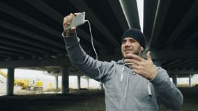 Boxer man having video chat on smartphone with friends after workout at urban location outdoors in winter. Tracking shot of Boxer man having video chat on Stock Image