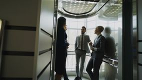 Tracking shot of businesswomen and businessmen colleagues talking in elevator and prepare to move down in modern. Business center indoors stock video footage