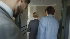 Tracking shot of Businesswomen and businessmen colleagues talking in moving elevator and come out from it and walking in. Hall in modern business center indoors stock footage