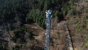 Communications tower in the forest - aerial view. Tracking shot of a communications tower in the forest - aerial view, winter time stock footage