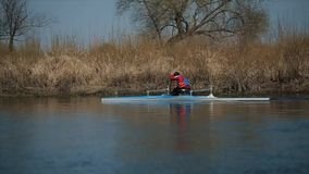 Tracking shot of Disabled sportsman rowing on the river in a canoe. Rowing, canoeing, paddling. Training. Kayaking. Disabled sportsman rowing on the river in a stock video