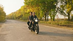 Tracking shot of handsome man in sunglasses riding a motorcycle with his girlfriend behind, traveling together on the. Asphalt road in forest in autumn stock video