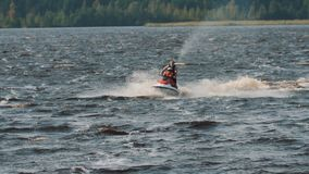 Tracking shot of man and boy in life vest ride a jet ski on hight speed stock footage
