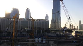 Tracking shot of modern city buildings with cranes, Dubai, United Arab Emirates stock video footage
