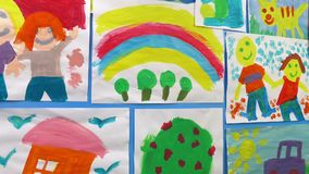 Passing Kid`s Paintings On Wall. Tracking shot moving past colorful children`s paintings on wall stock footage