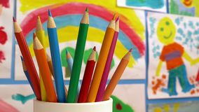 Color Pencils In Classroom With Paintings On Wall. Tracking shot moving past coloring pencils in children`s classroom with paintings on the wall stock footage