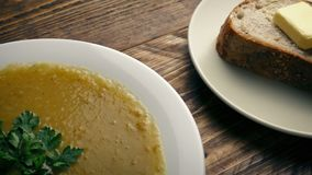 Bowl of soup and bread on wooden table. Tracking shot moving slowly past a bowl of soup next to a plate of bread and butter stock footage