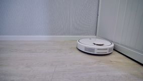 A tracking shot of a round robotic vacuum cleaner. stock video