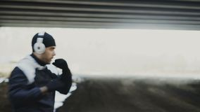 Tracking shot of sportive man boxer in headphones doing boxing exercise in urban location outdoors in winter stock video