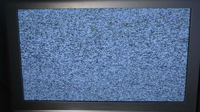 Tracking shot of TV screen with noise. Dolly shot of  TV screen with noise in dark room stock video