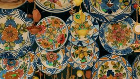 Tracking shot typical hand-painted majolica plates hung in a market in Valencia, Spain stock video footage