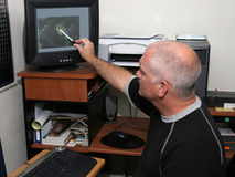 Tracking The Storm. A meteorologist tracking a hurricane on his computer and pointing out the eye. (focal point is his head/face Royalty Free Stock Photos