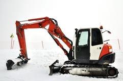 Tracklaying ekskawator na szczyciefal tg0 0n w tym stadium śnieżnej góry Obrazy Royalty Free