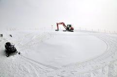 Tracklaying ekskawator na szczyciefal tg0 0n w tym stadium śnieżnej góry Zdjęcie Royalty Free