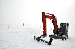Tracklaying excavator at top of snow mountain Royalty Free Stock Photos