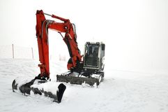 Tracklaying excavator at top of snow mountain Stock Photos