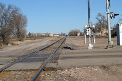 Tracks. Empty railroad tracks crossing a small town road stock image