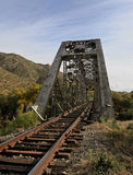 Tracks through the bridge. Rusty rails going through train bridge royalty free stock images