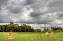 Tracks through a field with dramatic sky overhead. Tracks running through a grassy field in Warwickshire, England, with a dramatic cloudy sky overhead Royalty Free Stock Images