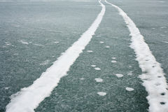 Tracks on Ice Surface. Vehicle tracks on ice surface of frozen lake Stock Photo