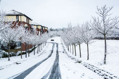 Tracks on road to residential area covered by snow Stock Photo
