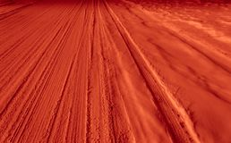 Tracks in snow. Coloured orange to add striking appeal. Line and texture in a winter setting Stock Photo