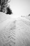 Tracks on snow covered road Royalty Free Stock Image