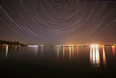 Tracks of stars in night sky. Above river Stock Photography