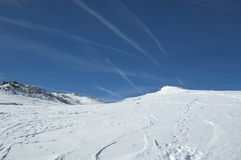 Tracks and trails. Colorado snow ski and tracks with con trails criss crossing the sky above Royalty Free Stock Images