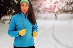 Красивая азиатская женщина в tracksuit бежит с улыбкой в парке в зиме стоковая фотография rf
