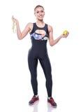 Tracksuit sportswear тонкой и здоровой молодой женщины нося держа ленту измерения и зеленое яблоко изолированными на белой предпо стоковое фото rf