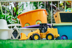 Tracktor toy car with toy boxes in the garden stock photography