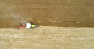Tracteur agricole labourant le champ avant de planter le blé d'OGM banque de vidéos