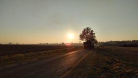 Tracteur avant un coucher du soleil Photographie stock