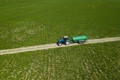 Tracteur avec le champ de fertilisation de remorque avec l'engrais naturel photos stock