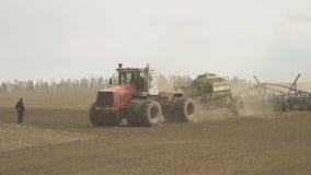 Tracteur avec le stockage de remorque pour le foret de grain et de graine fonctionnant dans le domaine banque de vidéos