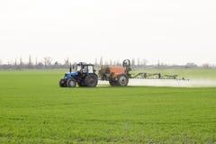 Tracteur avec un dispositif de jet pour l'engrais finement dispersé Image stock
