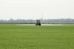 Tracteur avec un dispositif de jet pour l'engrais finement dispersé Photographie stock