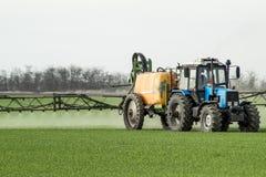 Tracteur avec un dispositif de jet pour l'engrais finement dispersé Image libre de droits