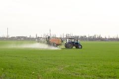 Tracteur avec un dispositif de jet pour l'engrais finement dispersé Photographie stock libre de droits